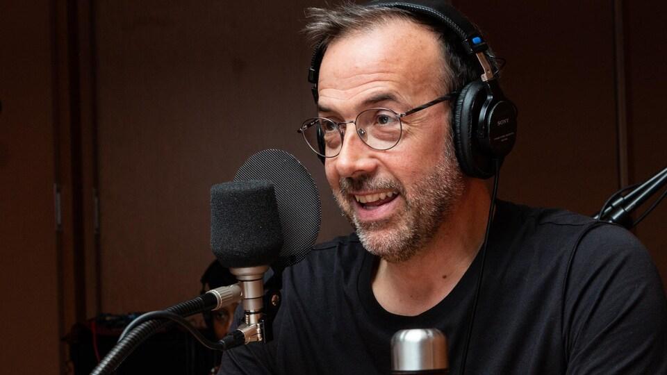 Le comédien à lunettes sourit à l'animatrice.