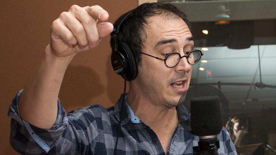 Le comédien devant un micro pointe avec l'index pendant la lecture.