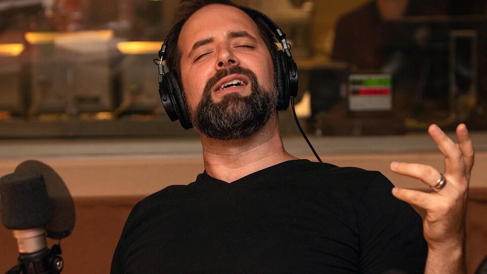 Un homme avec des écouteurs chante dans un studio de radio.