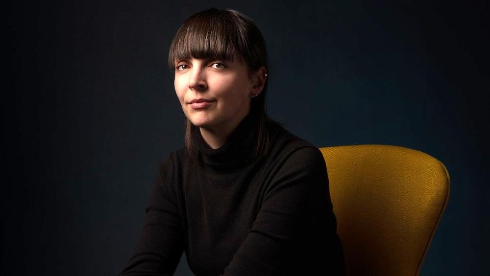 Kristina Gauthier-Landry est assise sur un fauteuil et regarde la caméra.