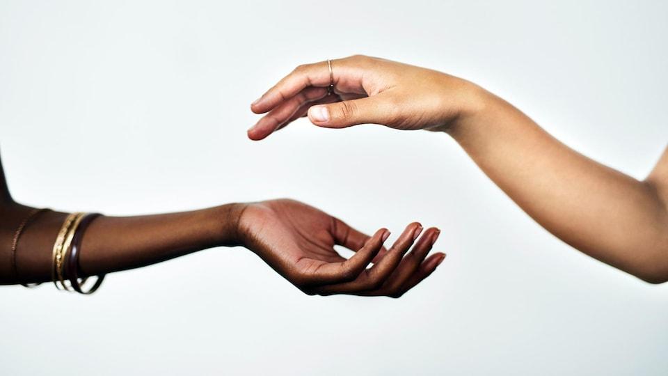 Les mains de deux femmes sont sur le point de se toucher.
