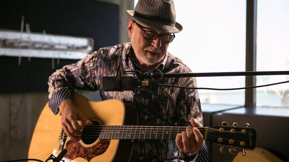Patrick Norman joue de la guitare dans un studio de radio.