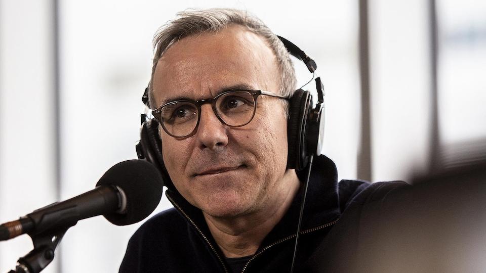 Un homme portant des écouteurs est devant un micro.