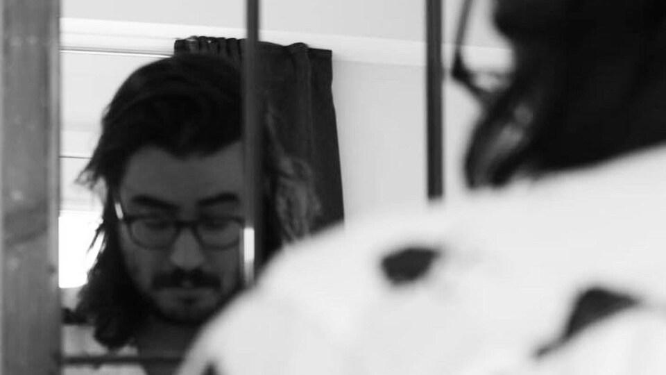 L'auteur est vu chez lui, posant face au miroir.