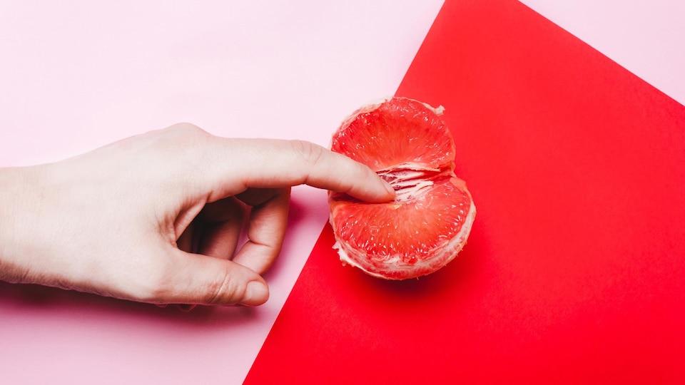Image conceptuelle d'un doigt dans un quartier d'orange, afin de représenter la sexualité féminine.