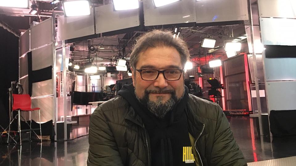 Manuel Ferreira porte des lunettes et sourit devant le plateau télé de CBC.