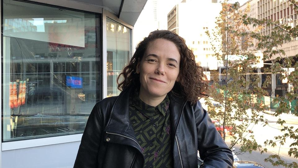 Elle porte un manteau en cuir noir et sourit sur un balcon qui montre la rue Georgia à Vancouver.