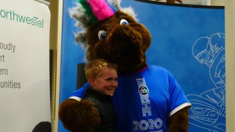 La mascotte Däch'äw des Jeux de l'Arctique 2020 avec son créateur.
