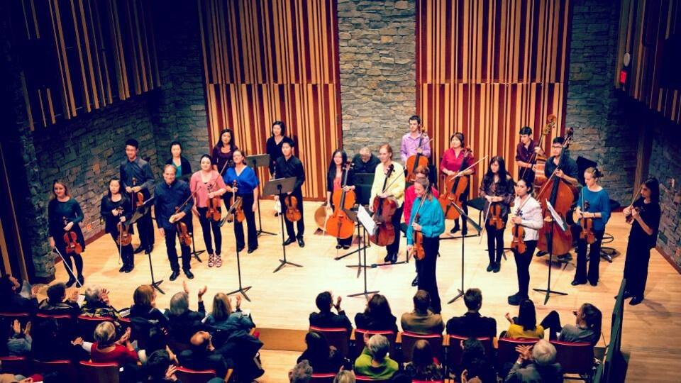 Un orchestre de chambre à cordes reçoit les applaudissements du public.