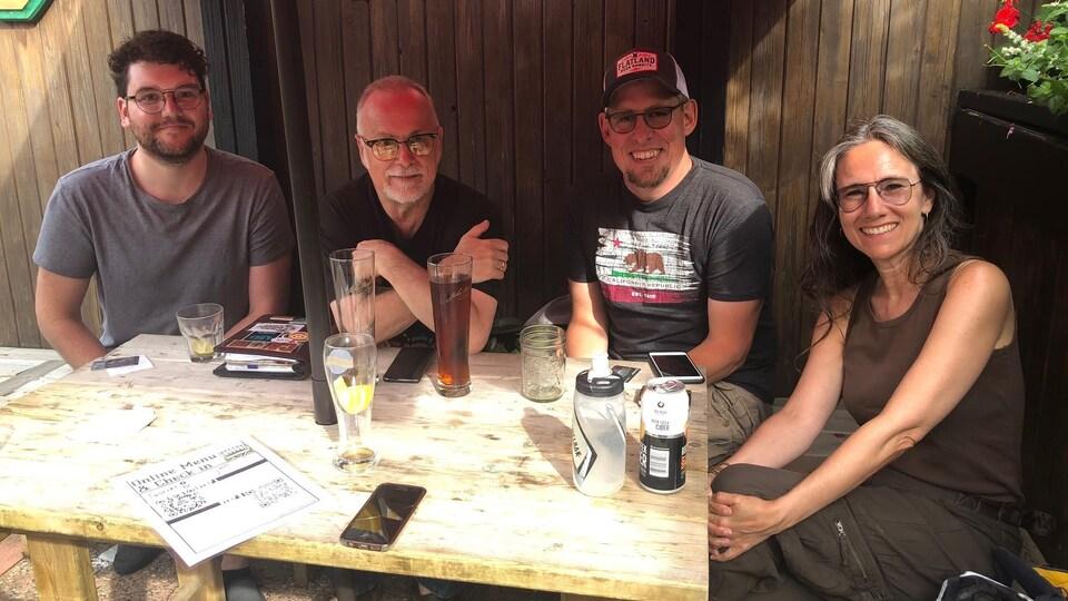 Quatre personnes assises autour d'une table en bois, à l'extérieur.