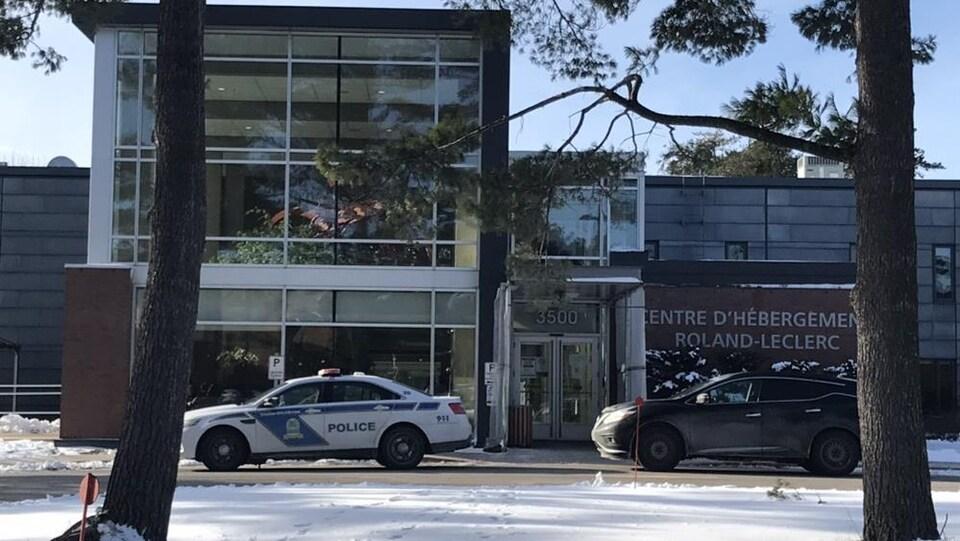 Une voiture de police devant un bâtiment avec l'inscription « Centre d'hébergement Roland-Leclerc ».