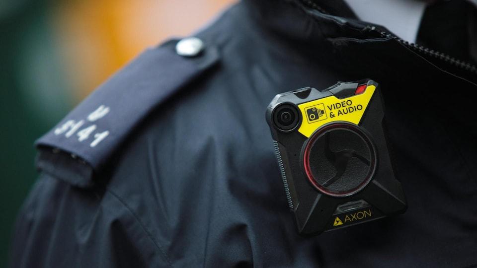 Une caméra accrochée au col de l'uniforme d'un policier.