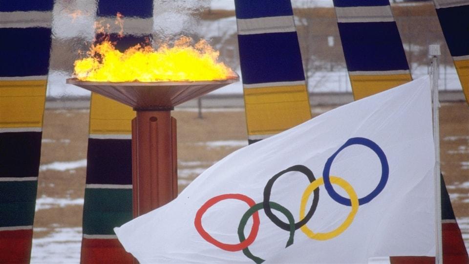 Un drapeau blanc paré des anneaux olympiques flotte devant la vasque de bronze où brûle la flamme olympique.