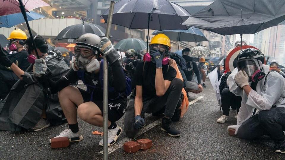 Des manifestants accroupis dans la rue.