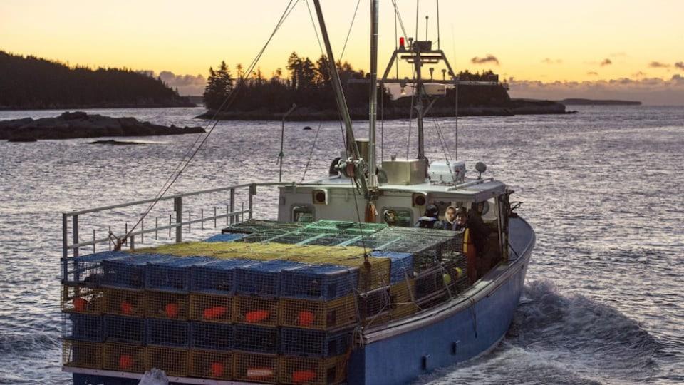 Le bateau vogue sur l'eau alors que le soleil se lève.