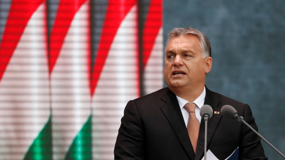 Viktor Orban debout devant un podium, des drapeaux hongrois en arrière plan.
