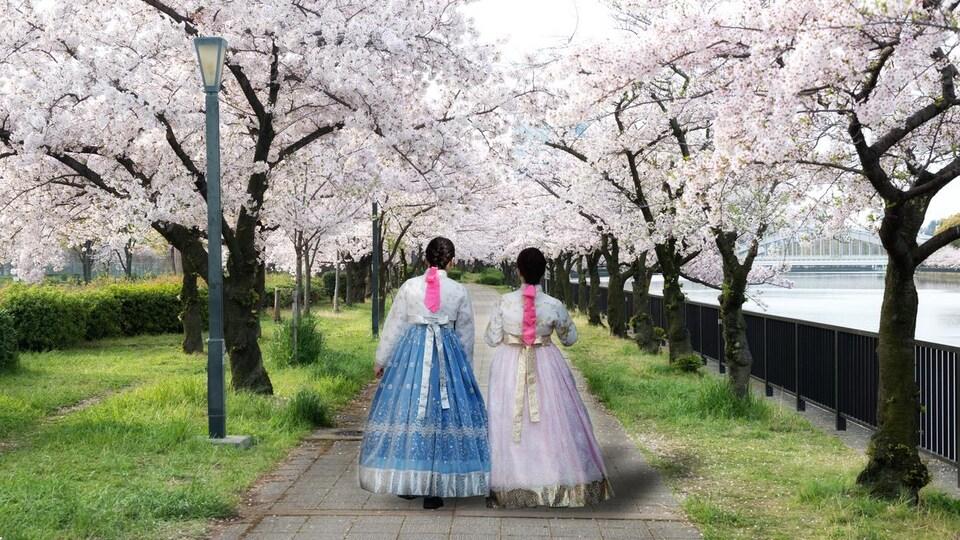 Deux femmes portant des robes rose et bleu dans un parc dont les arbres sont remplis de fleurs.