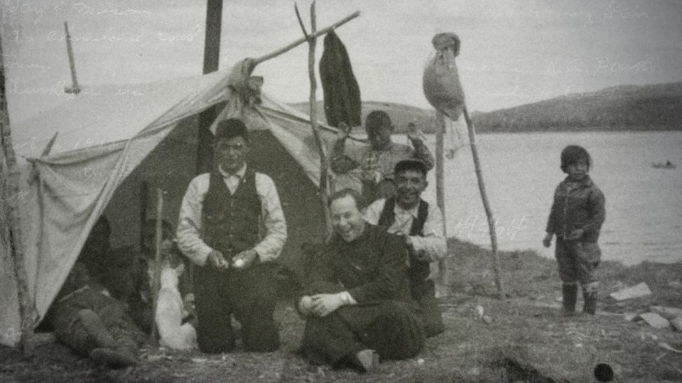 Le père Alexis Joveneau avec une famille innue. Ils sont tous assis près d'une tente, sur le bord de l'eau.