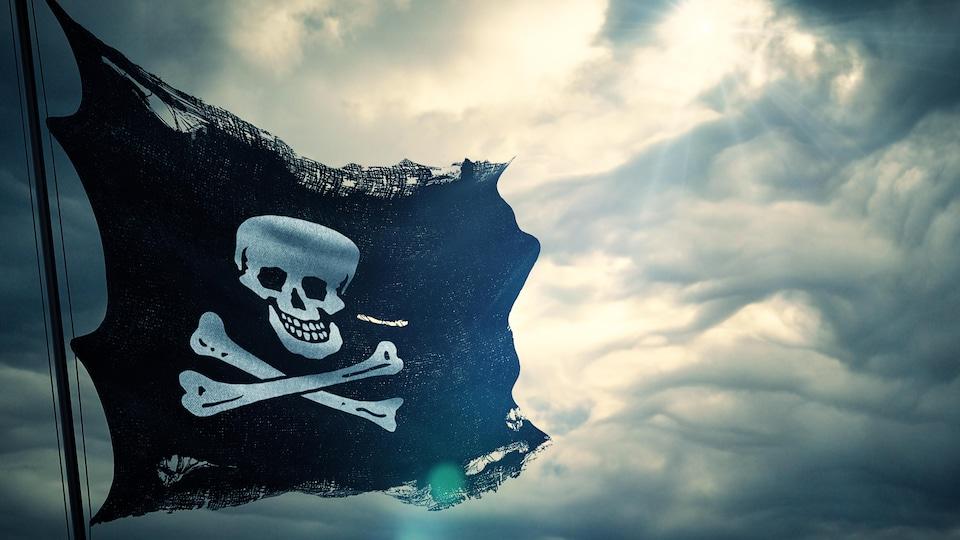 Un drapeau noir orné d'une tête de mort devant un ciel nuageux.