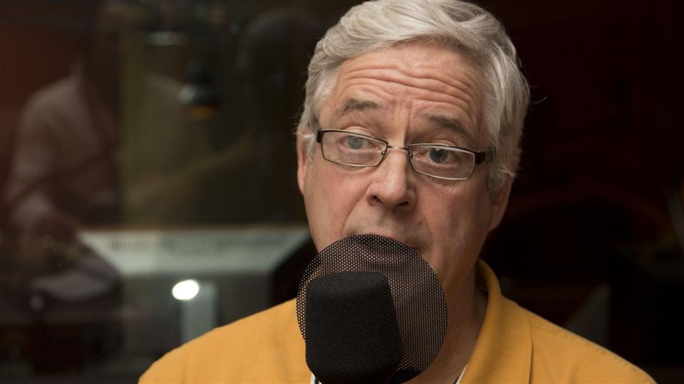Il parle derrière un micro noir dans un studio radio.