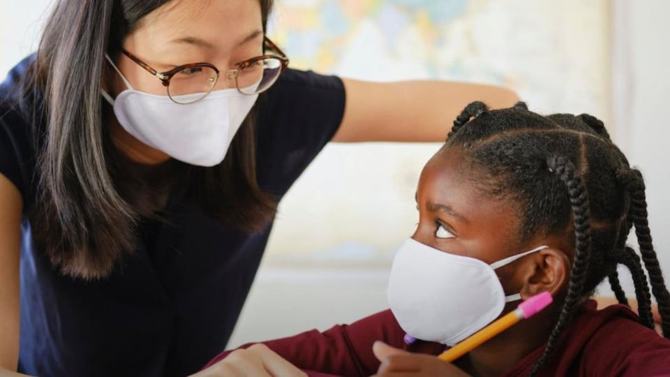 Une professeure parle à son élève. Les deux portent un masque.