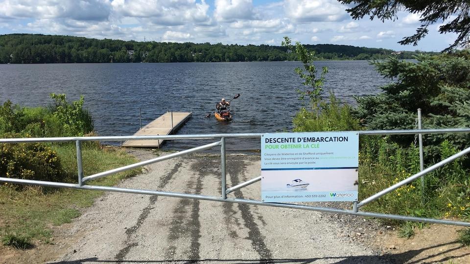 Une barrière barrant l'accès à un lac sur lequel se trouve un kayakiste.