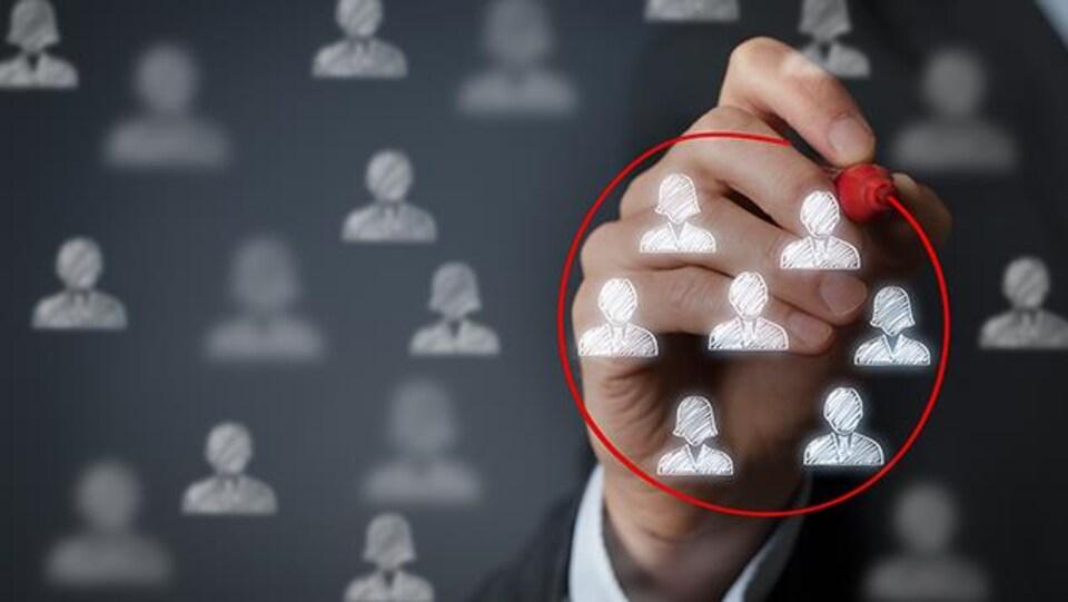 Une personne entoure avec un feutre un groupe de personne dessiné sur un tableau translucide.