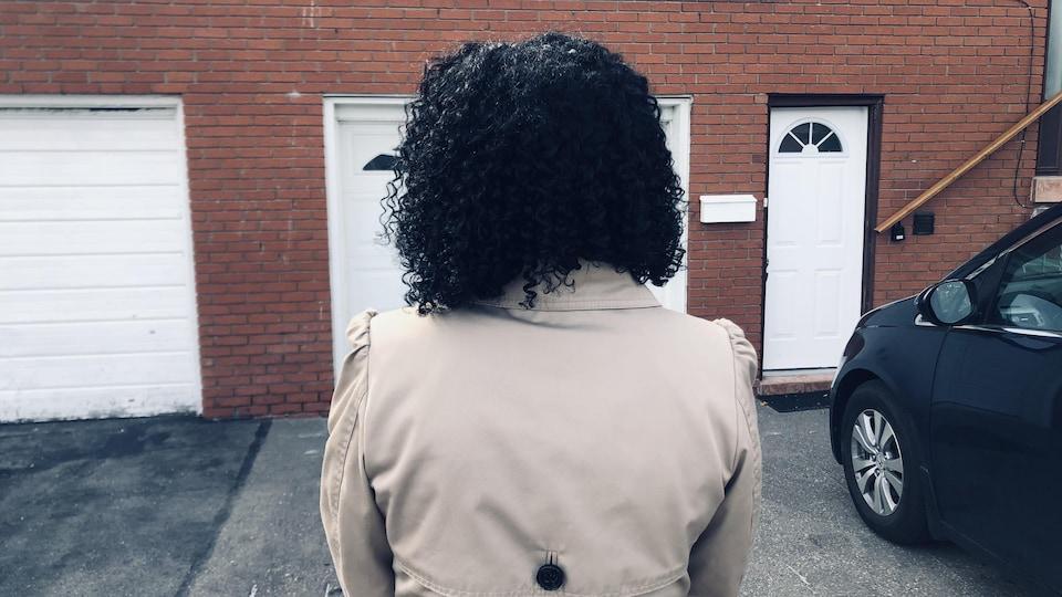 Une femme debout dans le stationnement devant la porte de son nouvel appartement.
