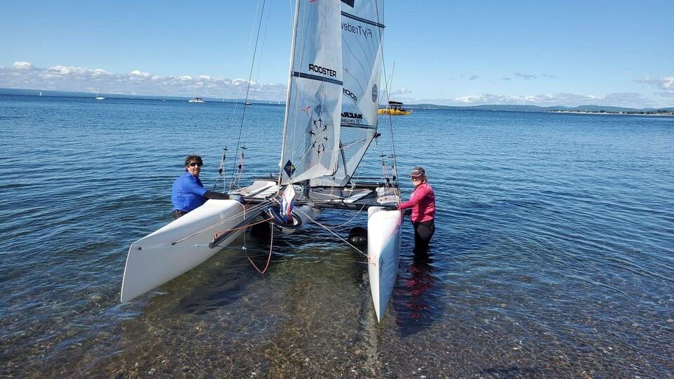 Des participants aux Régates s'affairent à une mise à l'eau de leur embarcation.