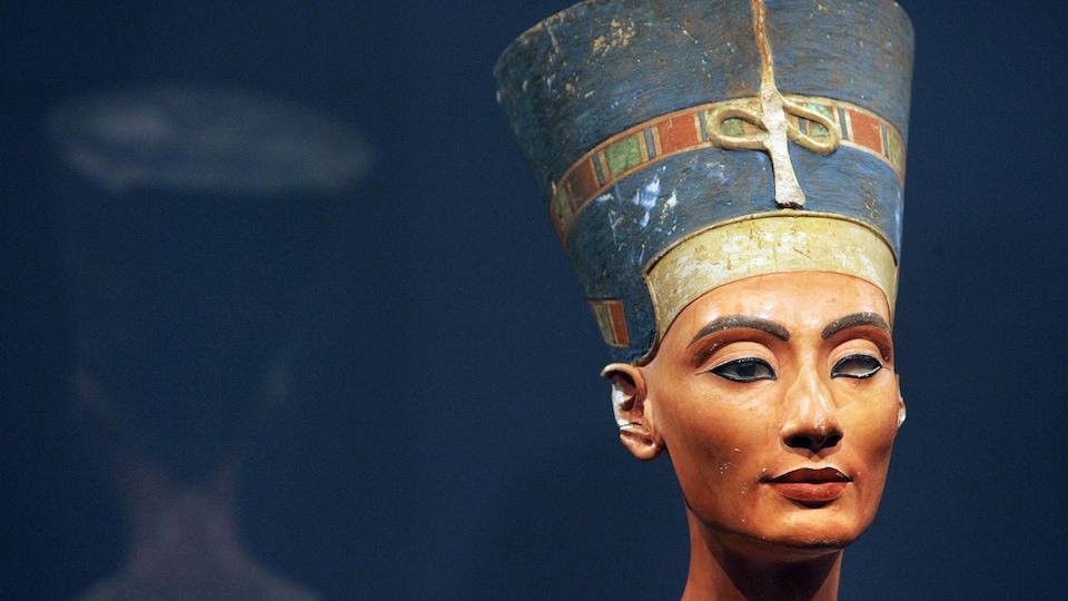 Une sculpture égyptienne représentant la tête de la reine avec un haut chapeau.