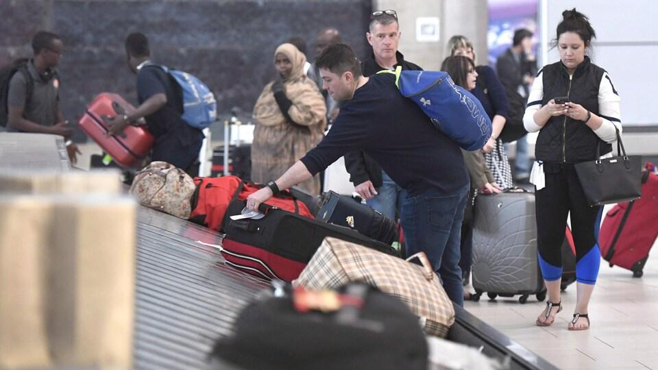 Des voyageurs récupèrent leurs bagages à l'aéroport d'Ottawa, en 2017.