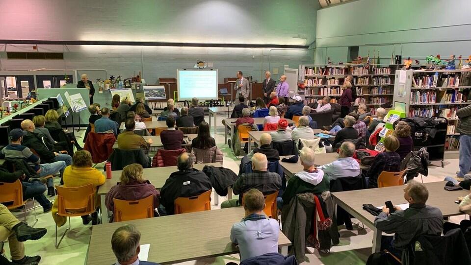 Des dizaines de personnes réunies dans une bibliothèque.