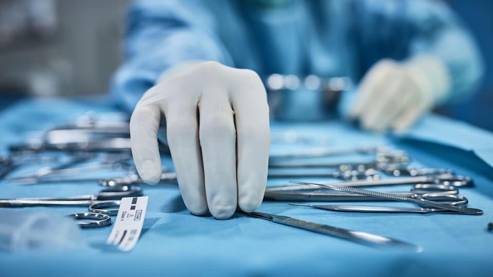 Le chirurgien prend un instrument chirurgical sur le plateau.