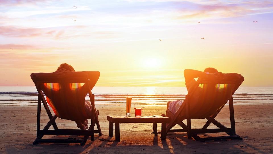 Un couple assis sur des chaises de plage profitent du soleil couchant.