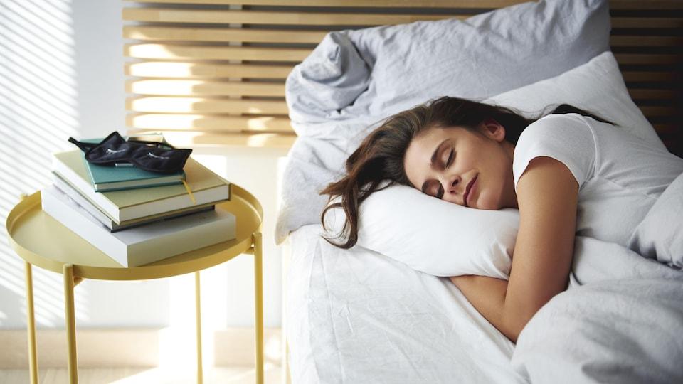 Une femme dort paisiblement sur un lit dans une chambre.