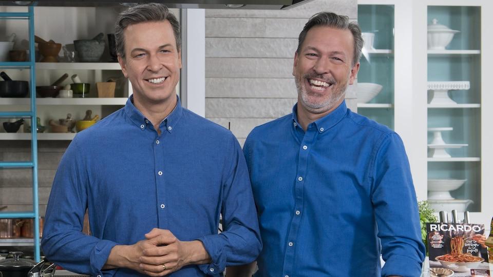 Le chef cuisinier porte les mêmes vêtements que son double de cire et sourit à la caméra.