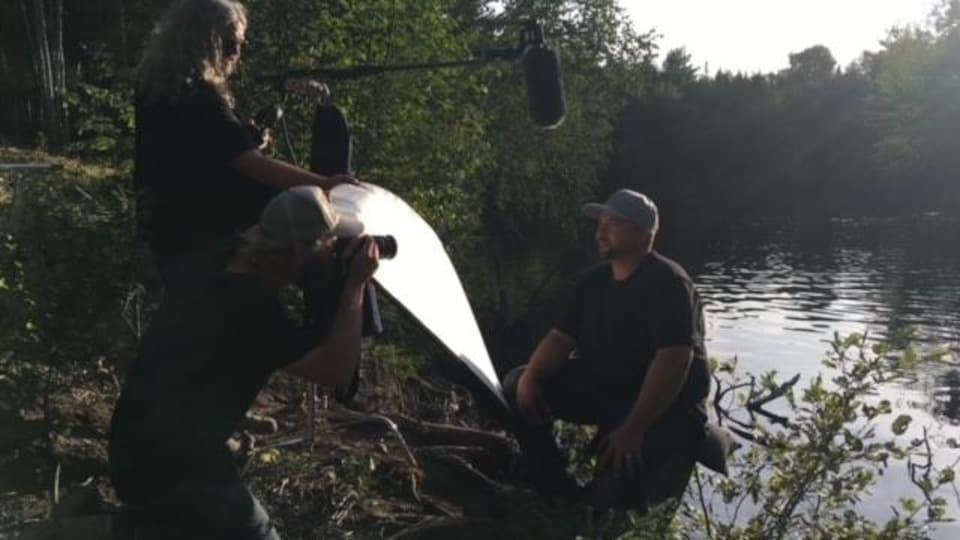 Un homme est assis sur le bord d'une rivière et est filmé par une équipe de tournage.