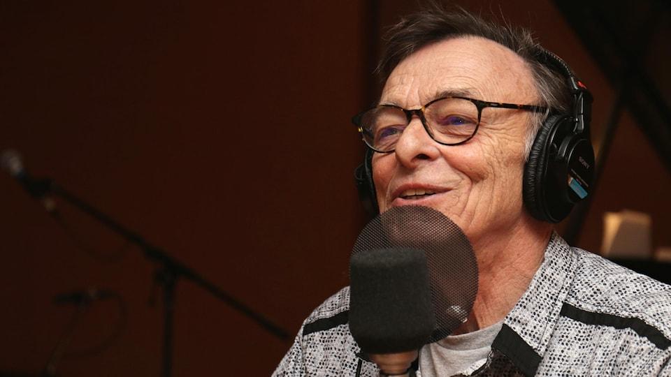 Robert Lalonde souriant dans un studio de radio.