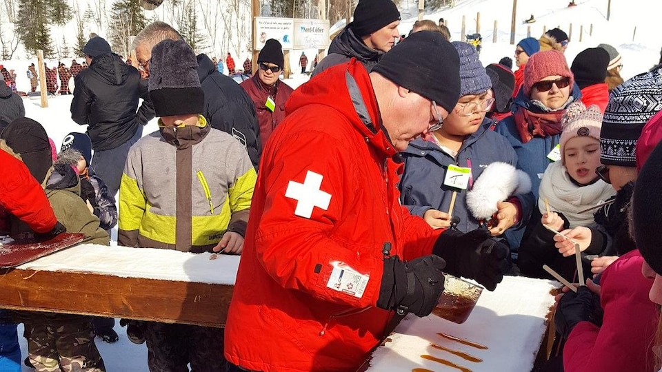 Robert Lavallée en train de verser de la tire d'érable sur la neige