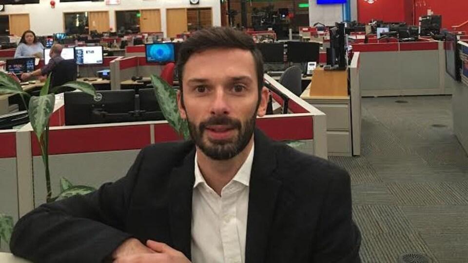 Romain Paulais est appuyé sur une paroie de séparation de bureaux dans une salle de nouvelles.
