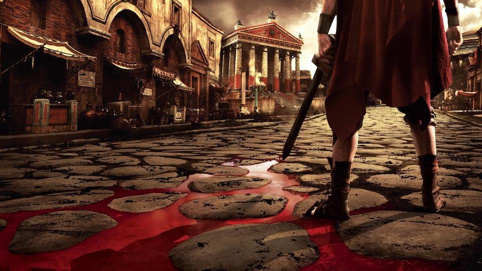 Un centurion tient un glaive devant un monument romain, alors que coule du sang à ses pieds.
