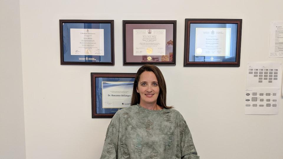 La chercheuse et orthophoniste Roxanne Bélanger assise dans son bureau devant ses diplômes.