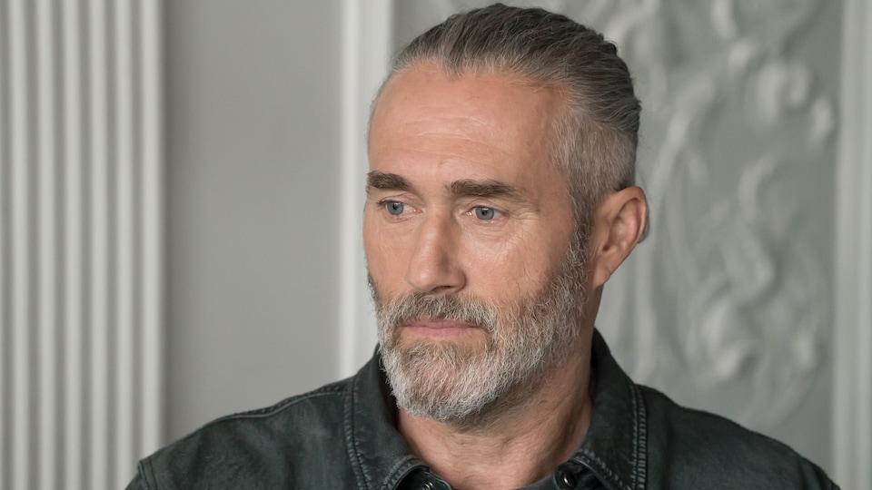 Un homme a le regard dans le vide. Il porte une barbe.