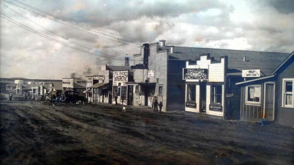 Une photo d'époque d'une rue avec de petits bâtiments en bois.