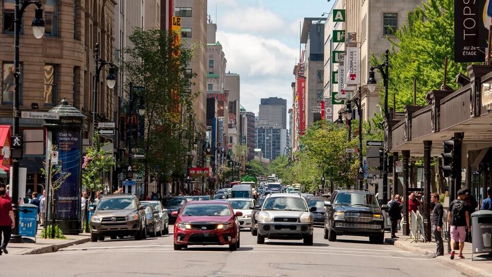 Des voitures et des piétons circulent sur une rue commerciale au centre-ville de Montréal.