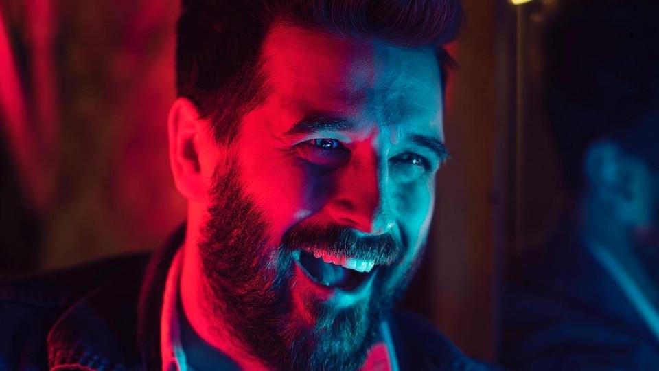 Ryan Doucette, sous des lumières bleues et rouges, tout souriant.