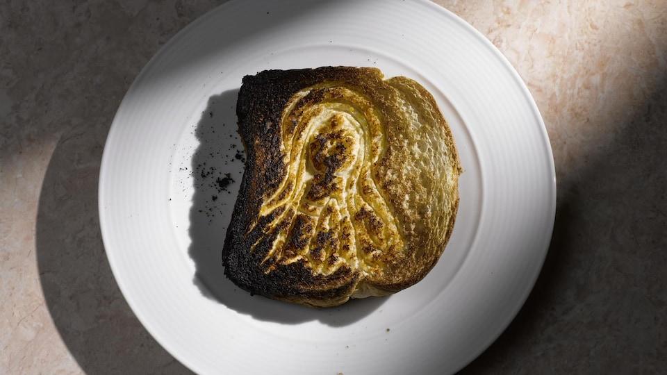 La rôtie repose dans une assiette sur un comptoir. Un rayon de lumière illumine le plat.