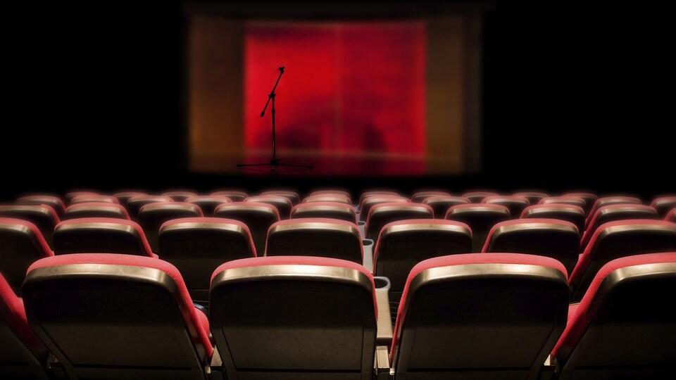 Une salle de spectacle vide avec des sièges rouges et un micro sur une scène également vide.