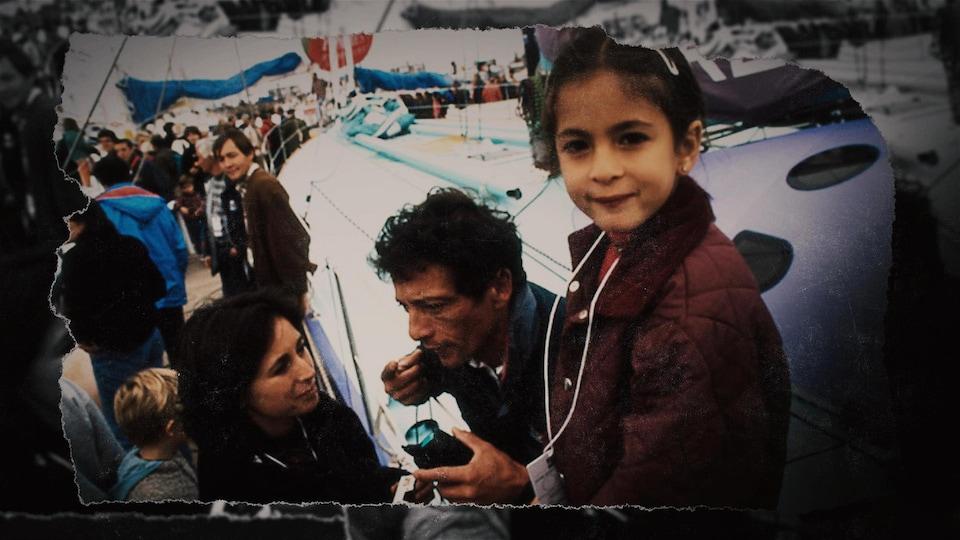Près d'un voilier, Gerry Roufs parle à Michèle Cartier, tandis que leur fille Emma regarde la caméra.