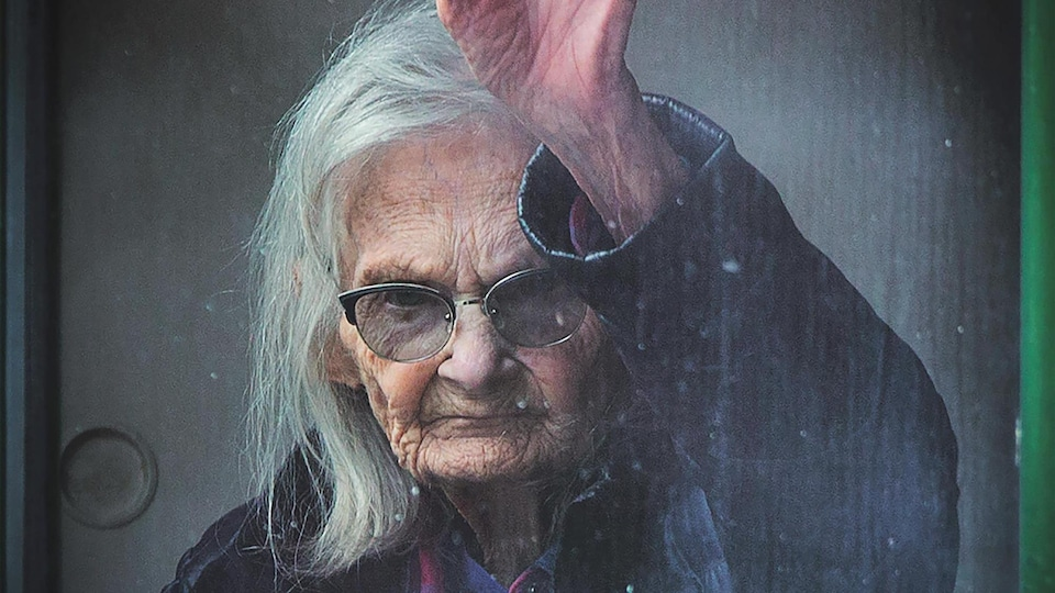 Sur la page couverture du livre Covid-19. 100 jours de confinement, de Jacques Nadeau, une femme âgée envoie la main.